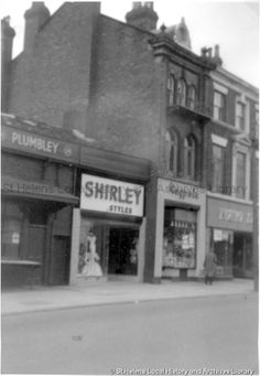 MSE/2/8/4 Black and white photograph showing the frontages of Shirley Styles, Plumbley and Maypole, Church Street, St.Helens c. 1960 . . . . . . MSE - The Frank Sheen Collection 2 - Photographs showing various buildings, events and housing in St.Helens. 8 - Photographs showing shops in the St.Helens area