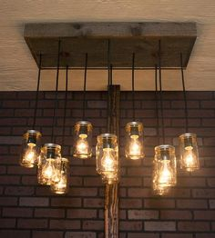 Crafted with reclaimed wood and clear Mason jars, this rustic light fixture adds a homey glow to any room. The rectangular canopy mounts flush to the ceiling and features 10 pendant lights, where the bulbs are encased in glass jars. Hanging at different lengths, the Mason jars can accommodate regular incandescent, fluorescent or Edison bulbs, just pick your favorite. Any way you light it up, the chandelier is sure to make a statement.