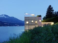 Warm lights welcome visitors to an Austrian boathouse. Thoughtful outdoor lighting highlights copper cladding at right and the sail design of the rooftop terrace shade.