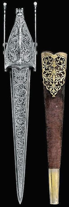 Indian katar (push dagger), 19th century, straight double-edged blade, completely silver-inlaid with a dragon's head and floral motifs, iron grip with side bands ending in the shape of drops, double transversal grip thickened at the center, pata-type hooded hand protection with a central rib and ending in the shape of a tiger's head in-the-round, original velvet sheath, brass cape fretworked with floral motifs, the chape was probably replaced.