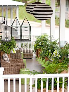 Extra-large planters full of ferns and creeping Jenny line the edges of this wide front porch creating a calm, natural feel. The green stools match the plants which echo the green of the landscaping. Rattan furniture also keeps with the nature-inspired theme. Boldly striped cushions on the seats and the stripes on the overhead lights add a modern kick to the space.