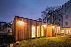 Pasivní dům ve vnitrobloku starších činžovních domů využívá některé dostupné přírodní principy. Na střeše majitel vybudoval kořenovou čističku. Provětrávaná fasáda s bezrámovými okny je obložená modřínovým dřevem.
