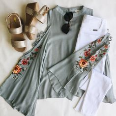 Floral Embroidered Bell Sleeve Top with Crisscross Sleeve Cutouts. Comes in black and dusty blue.