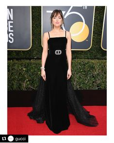Presenter at the 75th annual Golden Globes Dakota Johnson wore a #GucciPreFall18 organza  and velvet gown with crystal buckle and crystal embroideries on the train with satin platform  sandals. Dakota Johnson's black dress was in honor of the @TIMESUPNOW movement to support women in every industry who have experienced sexual harassment, assault, or abuse in the workplace. IG Gucci
