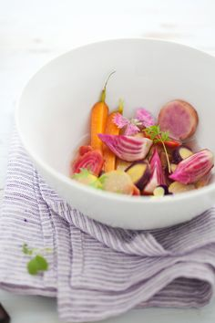 Purple, orange, red, and white carrots in the vegetable with aromatic herbs and edible flowers from Farmer Jones' Farm.