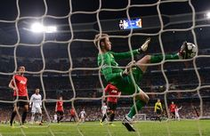 MADRID, SPAIN - FEBRUARY 13: David De Gea of Manchester United makes a save with his foot during the UEFA Champions League Round of 16 first leg match between Real Madrid and Manchester United at Estadio Santiago Bernabeu on February 13, 2013 in Madrid, Spain.