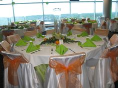 A wedding reception decorated in orange and lime green. The centerpieces contained gold fish surrounded by a wreath of flowers and greenery. The linens were green with a white topper.