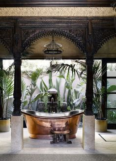 In this Martyn Lawrence Bullard-designed Malibu home, the copper tub in the master bath is by Waterworks, and the hanging lanterns, teak facade, and carved marble panel are Indian. Tour the rest of the home. Copper Tub, Global Decor, Outdoor Baths, Outdoor Showers, Indoor Outdoor, Home Decoracion, Malibu Homes, Up House, Interior Decorating