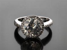 Ringweite: 53. Gewicht: ca. 5,5 g. WG 750. Klassisch-eleganter Ring mit einem Brillantsolitär, ca. 3,38 ct J/K VS, und einer Entourage von kleinen Brillanten,...