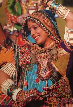 Indian dancer in colourful embroidery & bangles.