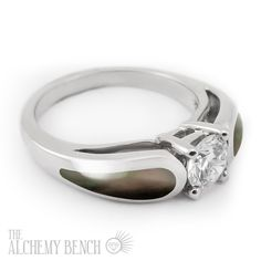 """""""Moonlit Mist - Horizon"""" This striking alternative engagement ring features lustrous black mother of pearl and a center diamond. Black mother of pearl is not a """"true black."""" It is a dark gray with beautiful notes of red and green depending on how the light hits it.  
