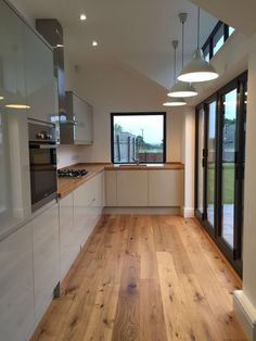 Stunning grey/green/sage gloss kitchen with oak tops and matching flooring.