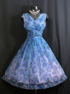 Description  An absolutely lovely 1950's party dress in exquisite shades of cobalt and sky blues with moss green on an impressionist print chiffon.