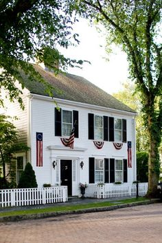 Nantucket charm with a white picket fencer and American flag banners hanging from the black shutter-framed windows.