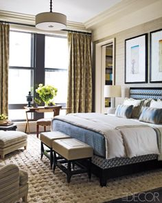 In a Manhattan home designed by Steven Gambrel, a master bedroom's custom-made bed is dressed with E. Braun & Co. linens, the writing table was designed by Ico Parisi, and the leather chair is vintage; the walls are covered in Indian silk, and the rug is from Sacco Carpets.