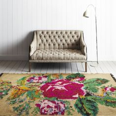 Very Large & Beautiful Rose/Floral Area Rug, looks very soft & the color palette or rich pink, soft pink, deep greens, & mustard yellow compliments the white wall & great Antique/Vintage high back loveseat Couch in a Earthy Sand color.