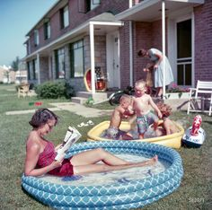 Woman relaxing in an inflatable swimming pool while her children play nearby in Park Forest, Illinois. 1954