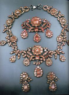 Conjunto de dois, algo já de eleição no barroco, pedras em tom pastel e metal em prateado. Preferencia por flores e laços