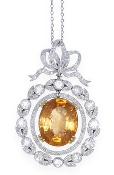 A belle époque topaz and diamond pendant, circa 1905 The cushion-shaped topaz within a garland surround, to a scrolling ribbon bow surmount, millegrain-set throughout with old brilliant-cut diamonds, on a fine chain, diamonds approximately 3.00 carats total, pendant length 4.7cm, chain length approximately 45.0cm