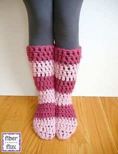 """The Strawberry Blossom Slipper Socks are soft, lofty, and extra cozy for toasty feet and legs. An easy to construct """"tube"""" sock is finished off with an extra (optional) drawstring and fun pompoms. One of the most fun things about this pattern are the fun stripes…I can't wait to see what colors you pick too!"""