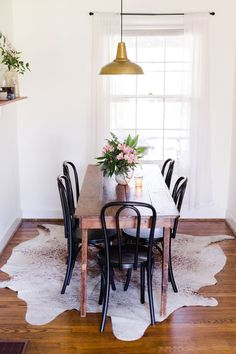Wood dining table with black bentwood chairs
