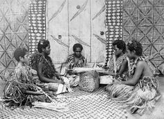 Group of young people making baskets. They are dressed in traditional Samoan dress. A tapa cloth hangs behind them.