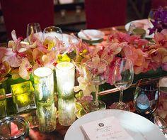 Low arrangements of pink and yellow phalaenopsis orchids are clustered with votive candles in mercury holders.