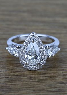 Custom Wedding Rings Custom Carat Pear Halo Diamond Engagement Ring - Encircled within a custom designed three-stone halo of sparkles sets a carat pear-cut diamond, shimmering in all of its glory. Titanium Wedding Rings, Wedding Rings Solitaire, Custom Wedding Rings, Halo Rings, Bridal Rings, Big Rings, Wedding Jewelry, Thing 1, Halo Diamond Engagement Ring