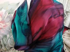 This gorgeous multi colored streaked scarf is hand painted and is 100% silk. Hand hemmed as well. Plum, Silk Teal, and Autumn Red all intertwine to