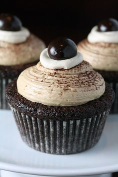 Mocha cake filled with coffee whipped cream topped with coffee buttercream and a chocolate covered espresso bean .