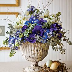 Pretty In Purple | For this festive centerpiece we grouped blue hybrid delphiniums and purple anemones against white stocks and tulips. Touches of silvery dusty miller and seeded eucalyptus provide contrast and texture, and succulents from a garden center give an unexpected twist. For a little height—without blocking the view—we added simple twigs from the yard.