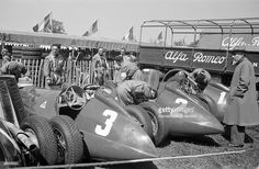 The British Grand Prix; Silverstone, May 13, 1950. The Alfa team cars in the paddock before the start. These are the cars of Luigi Fagioli,'Nino' Farina and Juan Manuel Fangio (l. to r.).