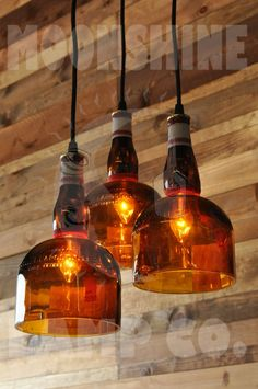 This is a 3-Lamp chandelier made from three hand cut Gran Marnier bottles. The front angle features the paper label, while the back side features the beautiful embossed glass. The bottles can be rotated, once the chandelier his hung in place. The ceiling canopy is an 8 round brass disc