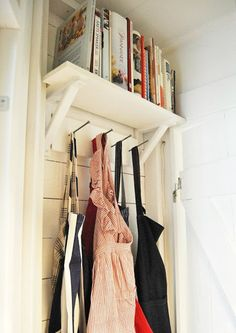 Cookbook shelf and apron hooks behind pantry door