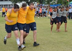 Gunner's Mate 2nd Class Kimberly Hernandez, Gunner's Mate Seaman Allison Casey, and Fire Controlman 1st Class Sean Causey, all assigned to the guided-missile destroyer USS Howard (DDG 83), participate in the three-person, four-legged race during Sports Day at Nong Prue Municipality Sports Field. Sailors assigned to Howard, the amphibious dock landing ship USS Tortuga (LSD 46), and the guided-missile frigate USS Reuben James (FFG 57) are participating in Sports Day.