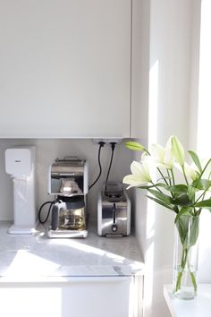 Homevialaura | White kitchen with marble countertop and white lilies
