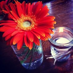 Simple Gebera Daisies in Bell Jars accompanied by floating candles is a perfectly simple wedding centerpiece.