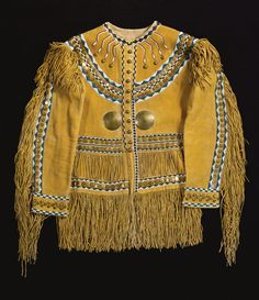 Western Apache Beaded and Fringed Tailored Hide Shirt styled in the manner of a US Army officer's military coat, worn by an Apache scout, with a yellow ochre pigment overall, panels of long fringe on the shoulders, sleeves, waist and hem, stitched in glass beadwork, with arrow-form elements radiating from a diamond chain on the collar