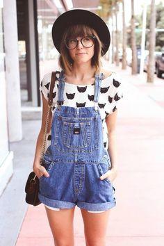 Shop the look: Lässiger Look durch ein Weiß/ Schwarz bedrucktes T-Shirt mit Rundhalsausschnitt und einer Blauen kurzen Latzhose aus Jeans. Dazu ein Hut - und fertig ist das perfekte Outfit.