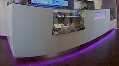 WIMPY'S, design per bar, la laccatura in Adamantx® color crema è messa in risalto da una linea rastremata verso il basso sino al collegamento con il battitacco in acciaio inox illuminato da luce led RGB. Anche la finestra con logo personalizzato nella parte destra del banco è illuminata da led, la parte superiore del top è ricoperta da un vetro fumè spessore 5mm.
