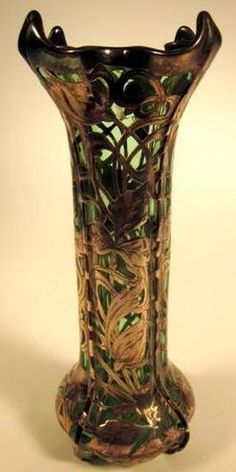 An Art Nouveau silver overlay green [art] glass vase, early 20th century, probably Loetz. Cylindrical form with wavy rim and bulbous base, overlaid in silver to show intertwining leaves.