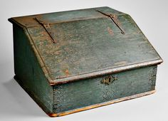 Skinner's - The Personal Collection of Lewis Scranton, Auction 2897M. May 21, 2016. Lot: 31.  Estimate: $4,000-6,000.  Realized: $20,000.   Description:  Blue/Green-painted and Carved Desk Box, New England, 17th century, constructed of oak and pine with molded lift top opening to two compartments, the front panel with chip-carved corners and punched geometric patterning, (hinges are old replacements), ht. 10 1/2, wd. 20, dp. 16 in. Hinges and lock catch replaced, missing lock, wear to…