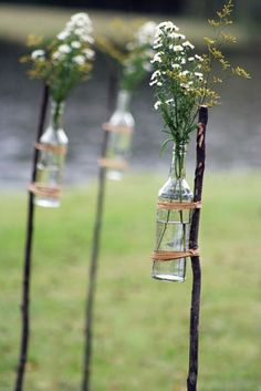 Straight sticks, repurposed bottles, twine + inexpensive flowers = a unique way to line a sidewalk or driveway for a party.