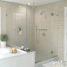 like the soft gray tile master drop in tub, glass shower FROM WATERWORKS: Polished nickel hardware and plumbing fixtures from the Aero line; Wall tile; Carrera marble floor and shower floor; Melissa sconce with black shade.