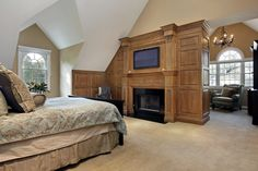 Bedroom divided into sleeping and relaxing sections by ornate wood fireplace surround with mounted TV above black hearth.