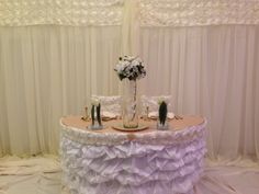 Incroyable Ivory Ruched Table Skirt On A Sweetheart Table With Ivory Backdrop Accented  With Ivory Ribbon Rose
