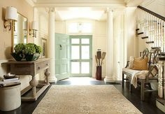 wide foyer with french feel, light turquoise front door, creamy walls, wall sconces, heavy light wooden long side table