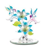"""Delicate and delightful, this glowing sculpture is a tribute to spring's incomparable beauty! Artfully fashioned from frosted and crystal-clear glass to create a scene of hummingbirds and blooms that delights the eye.  Weight: 0.1 lbs. UPC# 817515012745. 3 1/8"""" x 4"""" x 4"""" high. Glass."""