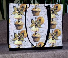"""Cupcakes, fairies and kitties!  This fun tote is 16"""" wide and 14"""" tall.  It has a bright red lining and inside pocket.  It also has feet for protection.  $105.00. Fairies, Totes, Cupcakes, Kitty, Bright, Pocket, Red, Kitten, Faeries"""