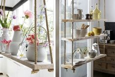 rustic shelves hung with rope. i especially love them in front of a window and the presence of light with the shelving.